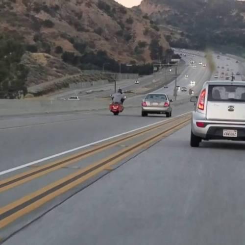 Un motorista provoca un espectacular accidente al pegar una patada a un coche